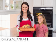 Купить «Surprised mother and daughter posing with roast turkey», фото № 6778411, снято 28 августа 2014 г. (c) Wavebreak Media / Фотобанк Лори