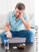 Купить «Hungover man with his medicine laid out on coffee table», фото № 6778427, снято 11 июня 2014 г. (c) Wavebreak Media / Фотобанк Лори