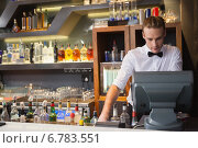 Купить «Handsome barman standing at the cash register», фото № 6783551, снято 27 июня 2014 г. (c) Wavebreak Media / Фотобанк Лори