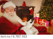 Smiling santa listening music with his smartphone. Стоковое фото, агентство Wavebreak Media / Фотобанк Лори