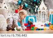 Купить «Мальчик играет в игрушки на фоне елки  и подарков», фото № 6796443, снято 11 декабря 2014 г. (c) Бандуренко Андрей / Фотобанк Лори