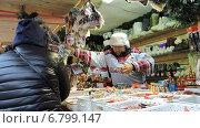 Купить «Продавец предлагает товар покупателю. ГУМ-ярмарка на Красной площади в Москве», эксклюзивное фото № 6799147, снято 13 декабря 2014 г. (c) lana1501 / Фотобанк Лори