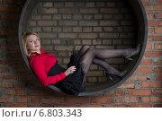 Молодая красивая женщина в коротком черном платье и красной блузке лежит в основании трубы в студии. Стоковое фото, фотограф Андрей Шарашкин / Фотобанк Лори