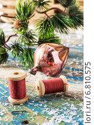 Купить «Катушки с нитками, стеклянная елочная игрушка и скрепки на фоне еловой ветки», фото № 6810575, снято 4 апреля 2020 г. (c) Николай Лунев / Фотобанк Лори