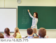 school kids and teacher writing on chalkboard. Стоковое фото, фотограф Syda Productions / Фотобанк Лори