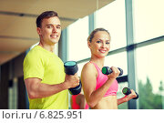 Купить «smiling man and woman with dumbbells in gym», фото № 6825951, снято 29 июня 2014 г. (c) Syda Productions / Фотобанк Лори