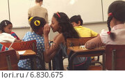 Купить «Pupils whispering secrets during class», видеоролик № 6830675, снято 23 августа 2019 г. (c) Wavebreak Media / Фотобанк Лори