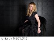 Молодая красивая девушка черном платье сидит на черном кресле. Стоковое фото, фотограф Анастасия Кузьмина / Фотобанк Лори