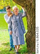 Купить «Счастливые бабушка и внучка стоят возле дерева в парке», фото № 6864035, снято 18 сентября 2014 г. (c) Константин Лабунский / Фотобанк Лори