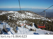 Кресельный подъемник на горнолыжном курорте на горе Олимпус, Тродос, Кипр в январе на фоне заснеженной горы с елками (2012 год). Стоковое фото, фотограф Алтанова Елена / Фотобанк Лори