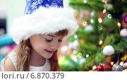 Купить «Девочка в синем колпаке возле новогодней елки», видеоролик № 6870379, снято 28 декабря 2014 г. (c) Кекяляйнен Андрей / Фотобанк Лори