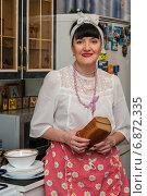 Купить «Счастливая женщина средних лет стоит с буханкой хлеба на домашней кухне», эксклюзивное фото № 6872335, снято 7 января 2015 г. (c) Игорь Низов / Фотобанк Лори