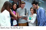Купить «Smiling friends standing and using tablet together», видеоролик № 6876211, снято 29 марта 2020 г. (c) Wavebreak Media / Фотобанк Лори