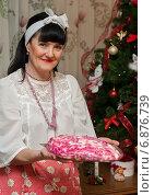 Купить «Счастливая женщина средних лет стоит с селёдкой под шубой на тарелке на фоне новогодней ёлки», эксклюзивное фото № 6876739, снято 7 января 2015 г. (c) Игорь Низов / Фотобанк Лори