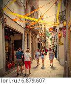 Купить «Люди на узкой улице Tossa de Mar, Каталония», фото № 6879607, снято 22 июня 2013 г. (c) Astroid / Фотобанк Лори