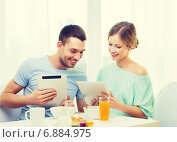 Купить «smiling couple with tablet pc reading news», фото № 6884975, снято 9 марта 2014 г. (c) Syda Productions / Фотобанк Лори