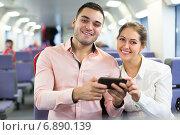 Young couple with smartphones in train. Стоковое фото, фотограф Яков Филимонов / Фотобанк Лори