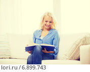 Купить «smiling woman reading book and sitting on couch», фото № 6899743, снято 6 февраля 2014 г. (c) Syda Productions / Фотобанк Лори