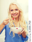 Купить «smiling woman with bowl of muesli having breakfast», фото № 6899759, снято 6 февраля 2014 г. (c) Syda Productions / Фотобанк Лори