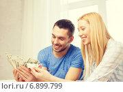 Купить «couple with money at home», фото № 6899799, снято 9 февраля 2014 г. (c) Syda Productions / Фотобанк Лори