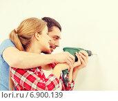 Купить «smiling couple drilling hole in wall at home», фото № 6900139, снято 26 января 2014 г. (c) Syda Productions / Фотобанк Лори