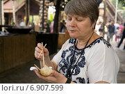 Купить «Женщина ест китайскими палочками рис приготовленный в бамбуке», фото № 6907599, снято 7 февраля 2014 г. (c) Алексей Маринченко / Фотобанк Лори