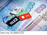 Купить «Мобильная связь. Сим-карты на фоне рублевых банкнот», фото № 6909575, снято 19 января 2014 г. (c) Sashenkov89 / Фотобанк Лори