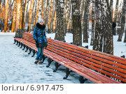 Купить «Девочка-подросток стоит возле длинной лавочки в зимнем парке отдыха», эксклюзивное фото № 6917475, снято 19 января 2015 г. (c) Игорь Низов / Фотобанк Лори