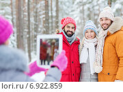 Купить «smiling friends with tablet pc in winter forest», фото № 6922859, снято 29 декабря 2014 г. (c) Syda Productions / Фотобанк Лори