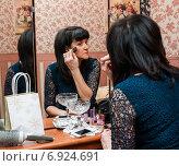 Женщина среднего возраста красит лицо кисточкой смотрясь в большое зеркало. Стоковое фото, фотограф Игорь Низов / Фотобанк Лори