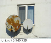 Купить «Спутниковые тарелки около окна на фасаде жилого дома», эксклюзивное фото № 6940739, снято 21 января 2015 г. (c) lana1501 / Фотобанк Лори