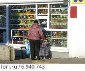 Купить «Покупатель у окошка продуктовой палатки на Уральской улице в Москве», эксклюзивное фото № 6940743, снято 21 января 2015 г. (c) lana1501 / Фотобанк Лори