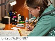 Купить «Школьница занимается выполнением домашнего задания дома», эксклюзивное фото № 6940887, снято 26 января 2015 г. (c) Игорь Низов / Фотобанк Лори