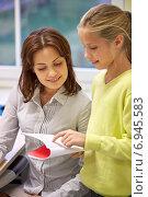 Купить «school girl with notebook and teacher in classroom», фото № 6945583, снято 15 ноября 2014 г. (c) Syda Productions / Фотобанк Лори