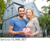 Купить «smiling couple holding piggy bank over house», фото № 6946367, снято 9 февраля 2014 г. (c) Syda Productions / Фотобанк Лори