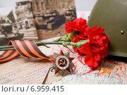 Купить «Орден Отечественной войны каска и фронтовые фотографии», фото № 6959415, снято 23 сентября 2018 г. (c) Igor Lijashkov / Фотобанк Лори