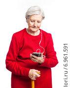 Старушка в красном платье слушает музыку через смартфон. Стоковое фото, фотограф Бандуренко Андрей / Фотобанк Лори