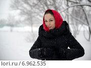 Молодая женщина в красном платке улыбается на фоне заснеженной улицы в снегопад. Стоковое фото, фотограф Андрей Шарашкин / Фотобанк Лори