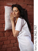 Девушка с подушкой около стены. Стоковое фото, фотограф Ivanikova Tatyana / Фотобанк Лори
