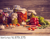 Купить «Preserved and fresh vegetables on wooden background», фото № 6979375, снято 5 апреля 2014 г. (c) Майя Крученкова / Фотобанк Лори