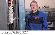 Купить «Мужчина электрик стоит возле высоковольтного шкафа управления и говорит в камеру», видеоролик № 6985927, снято 10 января 2015 г. (c) Кекяляйнен Андрей / Фотобанк Лори