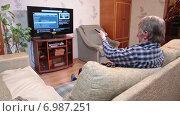 Купить «Мужчина смотрит телевизор в гостиной», видеоролик № 6987251, снято 11 января 2015 г. (c) Кекяляйнен Андрей / Фотобанк Лори