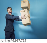 Купить «Surprised smart banker with the boxes», фото № 6997735, снято 10 апреля 2014 г. (c) Ingram Publishing / Фотобанк Лори