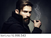 Artistic dark portrait of the young beautiful man. The young man smokes a tube. Стоковое фото, агентство Ingram Publishing / Фотобанк Лори