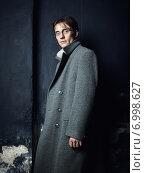 Artistic dark portrait of the young beautiful man in a gray coat. Стоковое фото, агентство Ingram Publishing / Фотобанк Лори