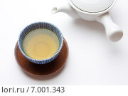 Японский зеленый чай в фарфоровой кружке на деревянном блюдце на белом фоне, и белый чайник (2014 год). Стоковое фото, фотограф Алексей Копытько / Фотобанк Лори