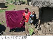 Купить «Деревня племени масаи в районе города Аруша, Танзания. Чернокожая африканская женщина с ребенком на руках стоит возле своей хижины», фото № 7017299, снято 14 февраля 2008 г. (c) Владимир Григорьев / Фотобанк Лори