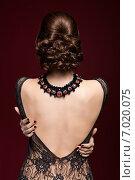 Young beautiful woman in black dress from back side on marsala color background. Стоковое фото, фотограф Serg Zastavkin / Фотобанк Лори