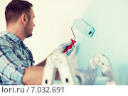 Купить «close up of male in gloves holding painting roller», фото № 7032691, снято 28 января 2014 г. (c) Syda Productions / Фотобанк Лори