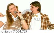 Купить «In slow motion happy geeky hipsters singing with microphone», видеоролик № 7064727, снято 19 августа 2019 г. (c) Wavebreak Media / Фотобанк Лори